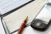 A pen and a mobile phone over a checkbook — Stock Photo