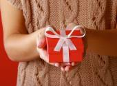 Female hand holding gift box isolated on red background — Stock Photo