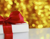 Christmas golden gift on a furry background — Stock Photo