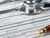 Stethoscope on medical billing statement on table, all text is — Stock Photo