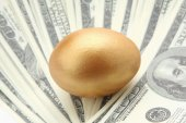 A golden egg on dollars — Stock Photo