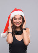 Attractive smiling woman in Santa Cap. Isolated over a gray background. — Stock Photo