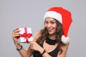 Woman in Santa hat holding gifts, isolated on gray background — Stock Photo