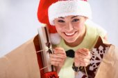 Happy girl on santa hat holding a shopping bag with gift box — 图库照片
