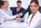 Beautiful young business people with colleagues discussing in the background — Stock Photo