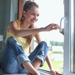 Woman painting wall of an apartment with a paintbrush carefully finishing off around window frame — Stock Photo #57112559