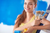 Happy beautiful young woman doing wall painting, sitting on ladder — Stock Photo