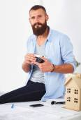 Portrait of male designer sitting on a table with blueprints and holding camera — Stock Photo