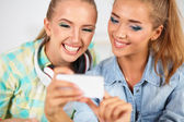 Two girls look on the phone photo together — Stock Photo