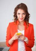 Beautiful businesswoman using cell phone standing in office — Stock Photo
