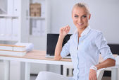 Attractive businesswoman sitting on a desk with laptop in the office — Stock Photo