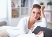 Giovane bella donna seduta sul divano in camera sua — Foto Stock