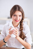 Young businesswoman sitting on the desk with cup in office — Φωτογραφία Αρχείου