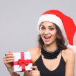 Woman in Santa hat holding gifts, isolated on gray background — Stok fotoğraf #57622515