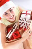 Happy girl on santa hat holding a shopping bag with gift box — Stock Photo