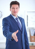 Business and office concept - handsome businessman with open hand ready for handshake — Foto de Stock