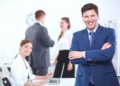 Successful business man standing with his staff in background at office — Stock Photo