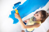 Happy beautiful young woman doing wall painting, standing — Stock Photo