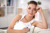 Pretty woman in her living room sitting on the couch sending messages — Stock Photo