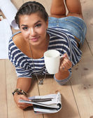 Portrait of female painter lying on floor near wall after paintingand holding a cup — Stock Photo