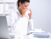 Young businesswoman blowing her nose, sits at the desk — Stock Photo