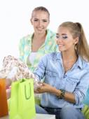 Two young women sitting with shopping bag at home — Stock Photo