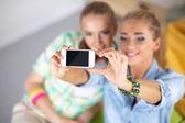Twee meisjes nemen van foto's op de telefoon thuis — Stockfoto