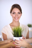 Beautiful woman holding pot with a plant, standing at home — Stock Photo