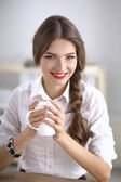 Young businesswoman sitting on the desk with cup in office — Foto de Stock