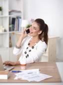Młoda kobieta siedzi przy biurku i rozmowy na telefon — Zdjęcie stockowe