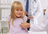 Female doctor examining child with stethoscope at surgery — Stock Photo