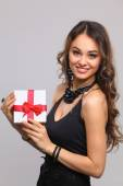 Young woman happy smile hold gift box in hands, isolated over grey background — Stock Photo