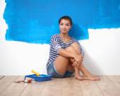 Happy beautiful young woman doing wall painting,sitting on the floor — Stock Photo