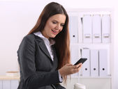 Smiling businesswoman holding disposable cup and smartphone — Stock Photo