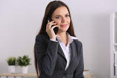 Smiling businesswoman talking on phone sitting at the office — Stock Photo