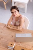 Attractive businesswoman sitting  on desk in the office — Stockfoto