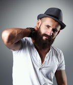 Portrait of handsome bearded man in hat standing , isolated on grey background — Stock Photo