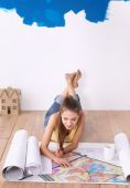 Young woman lying on the floor and looking at blueprint of new house — Stock Photo