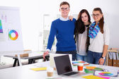 Young business people standing at office near desk — Stock Photo