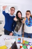 Young business people standing at office near desk and showing ok — Stock Photo