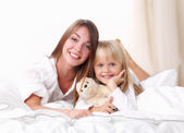 Woman and young girl lying in bed smiling — Stock Photo