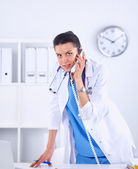 Young woman doctor in white coat at computer using phone — Stock Photo