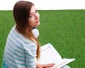 女人看书坐在绿色的草地上 — 图库照片