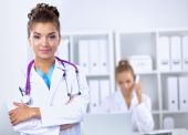 Portrait of young woman doctor with white coat standing in hospital — Stock Photo