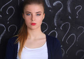 Young girl with question mark on a gray background — Stock Photo