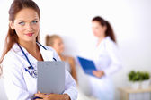 Smiling female doctor with a folder in uniform standing at hospital — Stock Photo