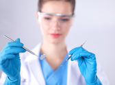 Attractive female dentist with tools , standing on gay background — Stock Photo