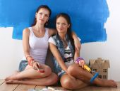 Two happy beautiful young women doing wall painting, — Stock Photo