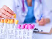 Woman researcher is surrounded by medical vials and flasks — Stock Photo