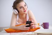 Young woman lying on floor and listen to music — Stock Photo